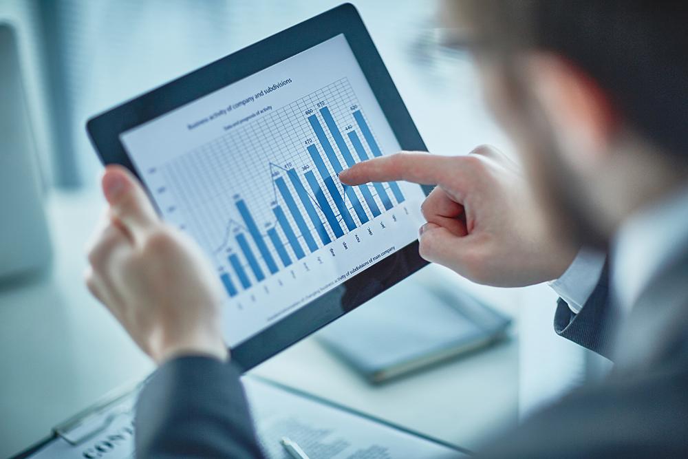 男性がアイパッドを使ってグラフで数値を見ている