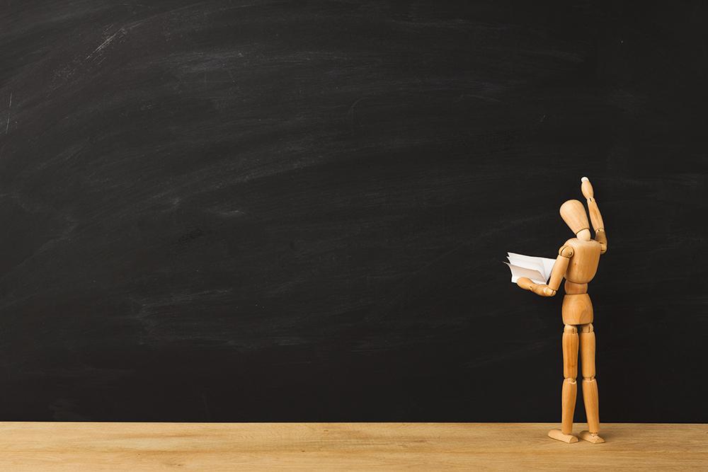 人形が黒板に何かを書こうとしている
