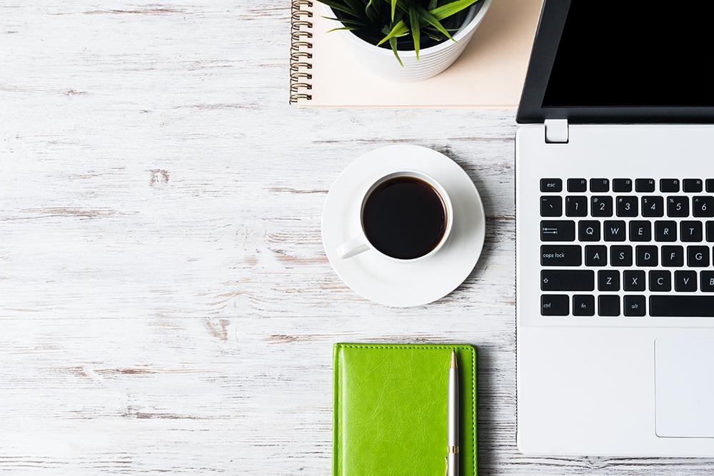 パソコンとコーヒーとノート、ペンがある