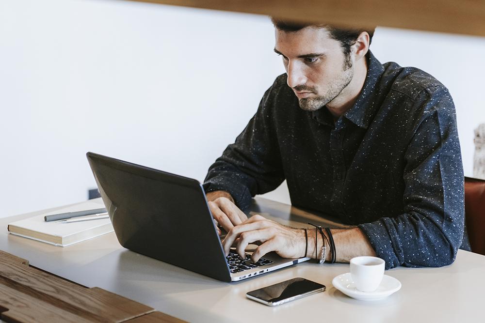 男性がパソコンを見ながら作業をしている