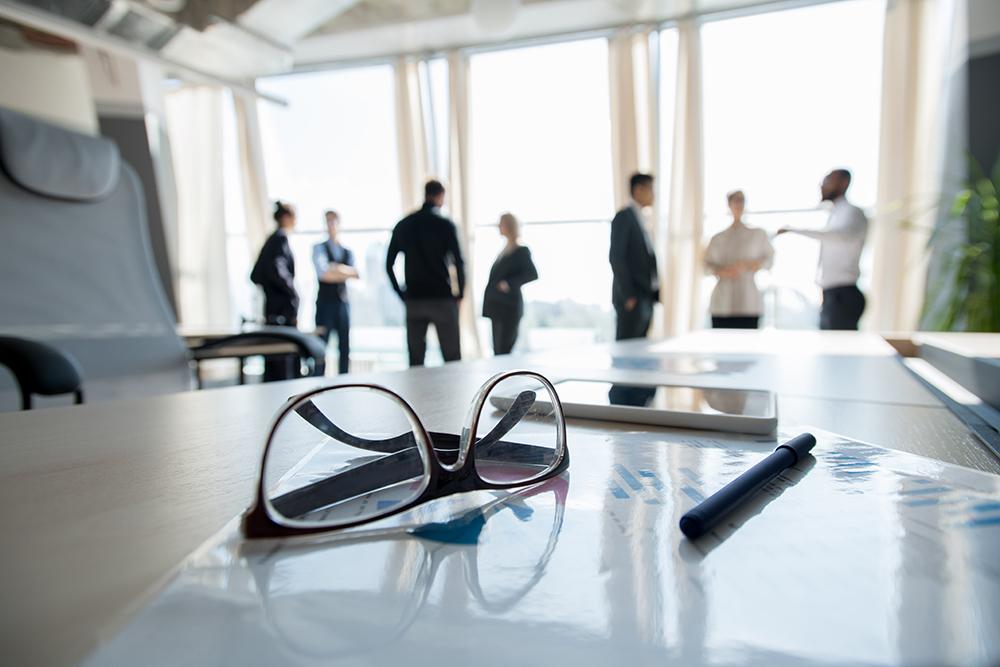 机の上に眼鏡が置かれていて、その奥では複数人の男女が話している