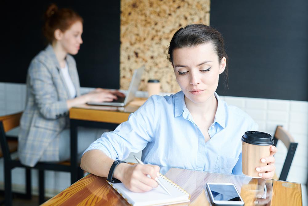 コーヒーを片手にカフェでノートに何かを書いている女性