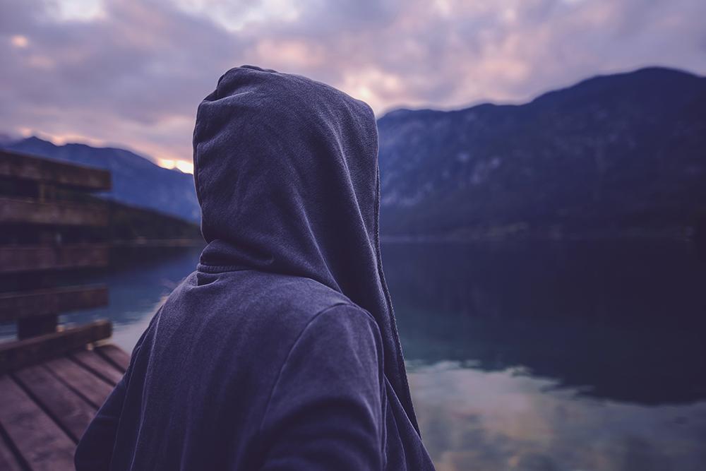 フードを被って顔が見えない人が湖畔を眺めている