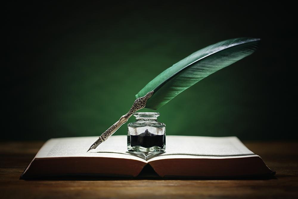 本の上にインクと羽ペンが置かれている