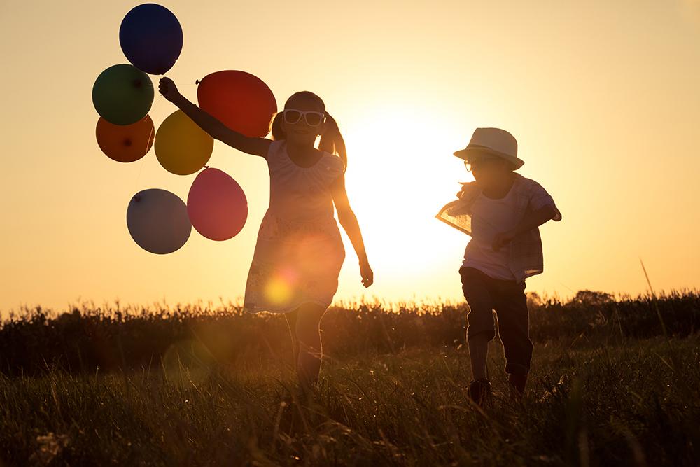 男の子と風船を持った女の子が夕日にてらされながら歩いている