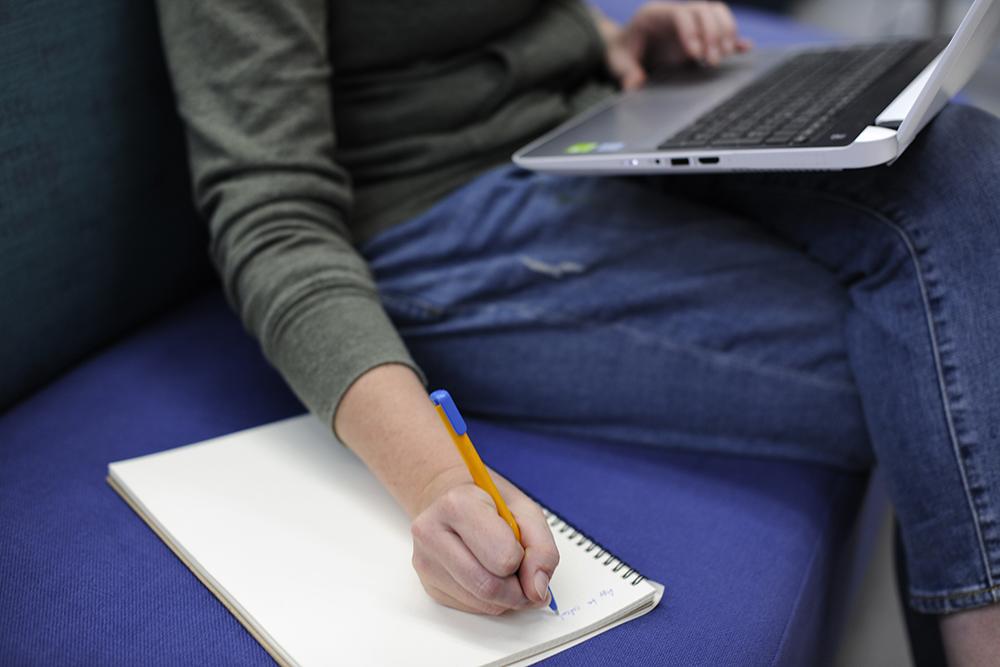 パソコンを使いながらノートにメモをしている