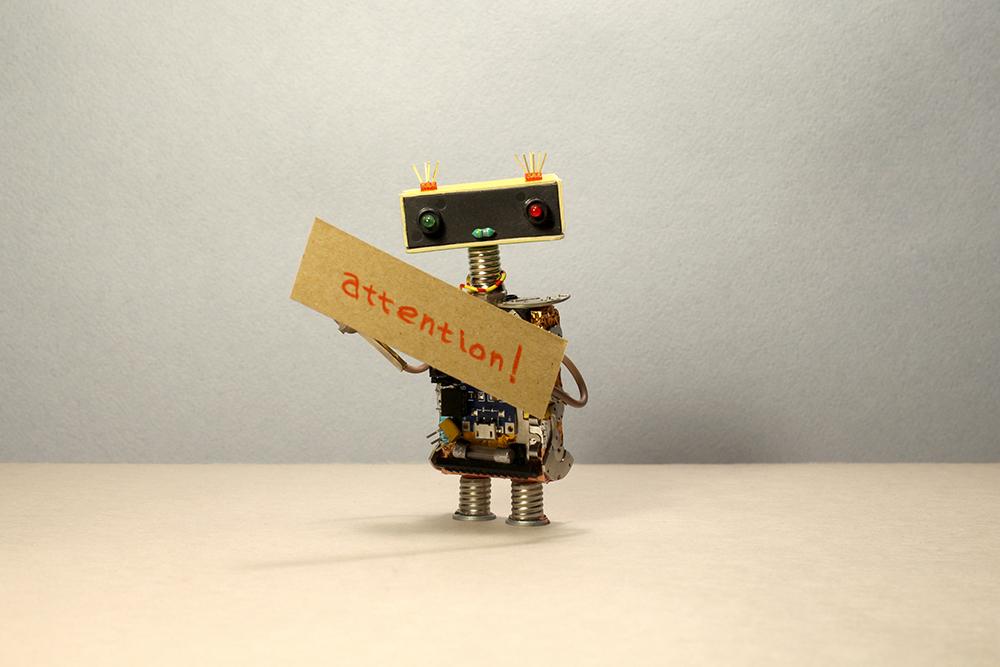 注目!という文字を持ったロボット