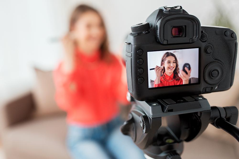 女性がカメラで動画を撮っている